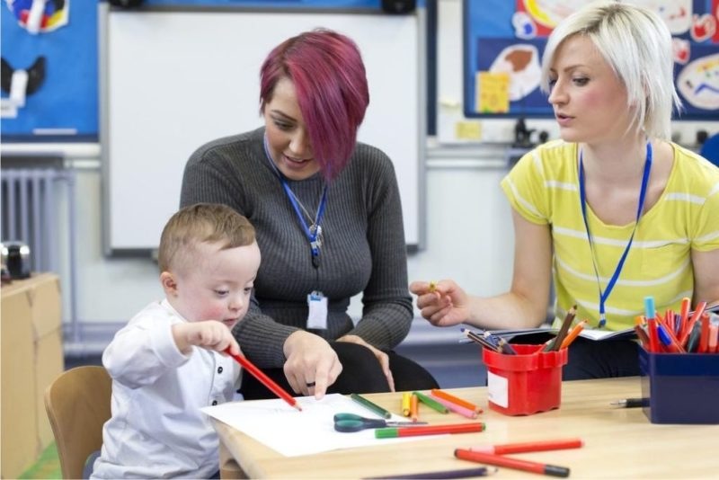Nursery teacher sitting with a parent and her Down Syndrome son in the classroom.