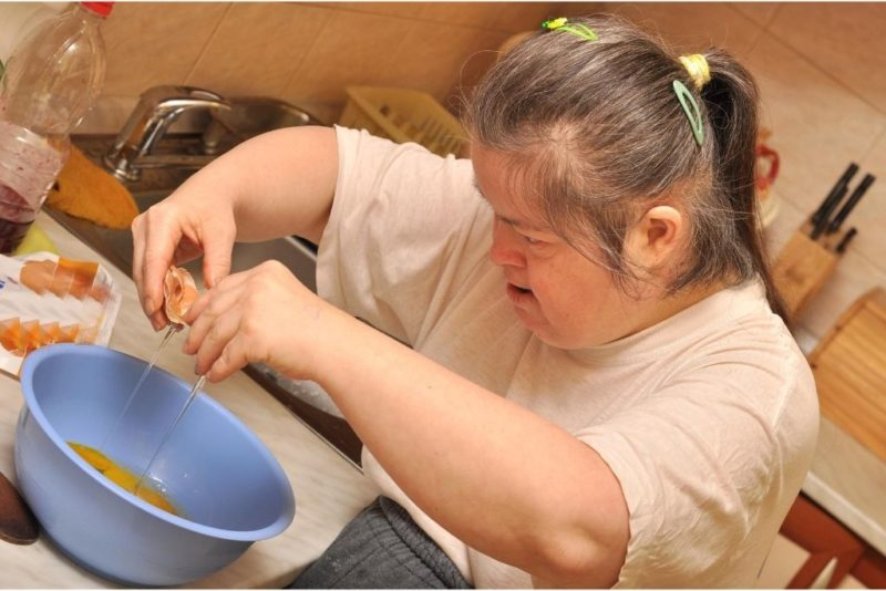 Woman with down syndrome cooking in the kitchen