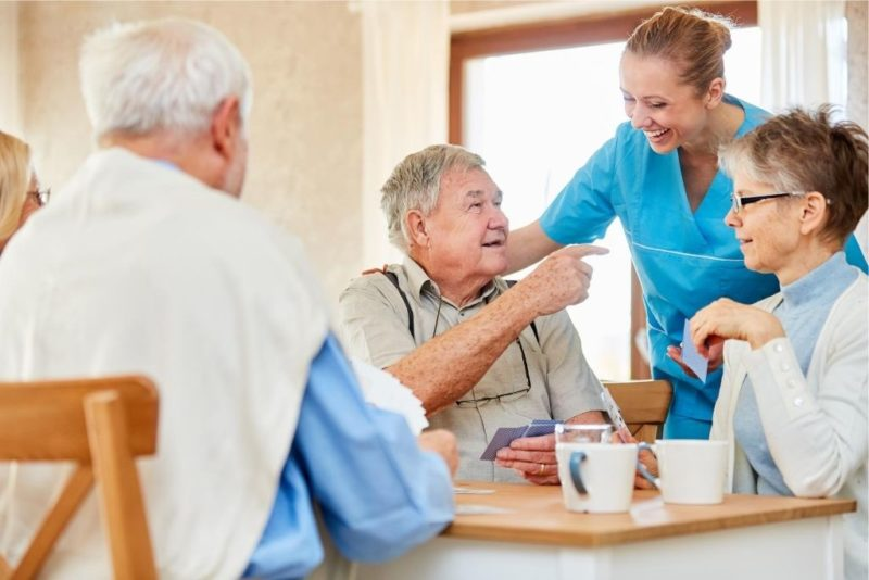 Nursing home care for seniors while drinking coffee and playing in the retirement home