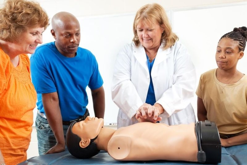 A nurse educator teaches a group about CPR