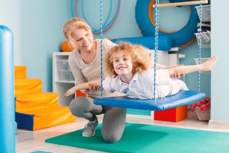 An occupational therapy assistant works with a young boy on a swing