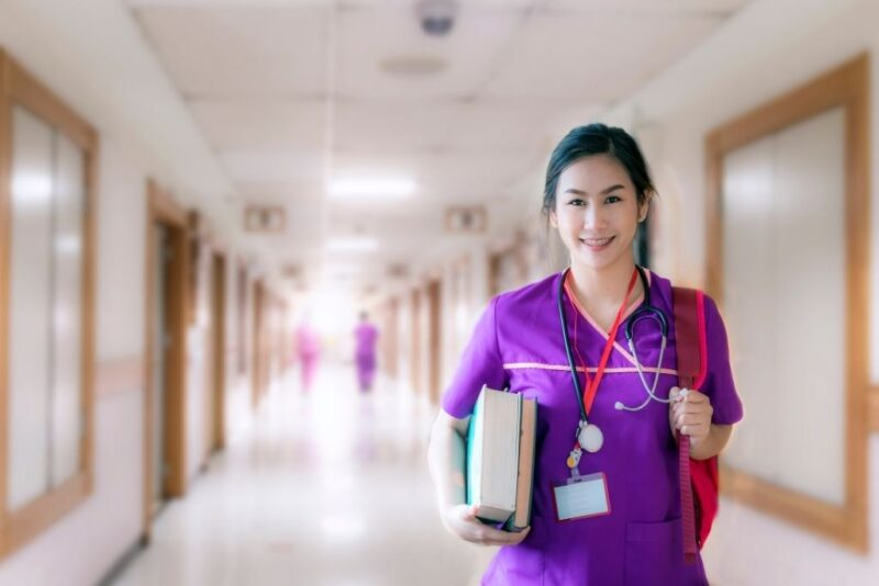 A nurse in purple scrubs carries books while earning a BSN degree