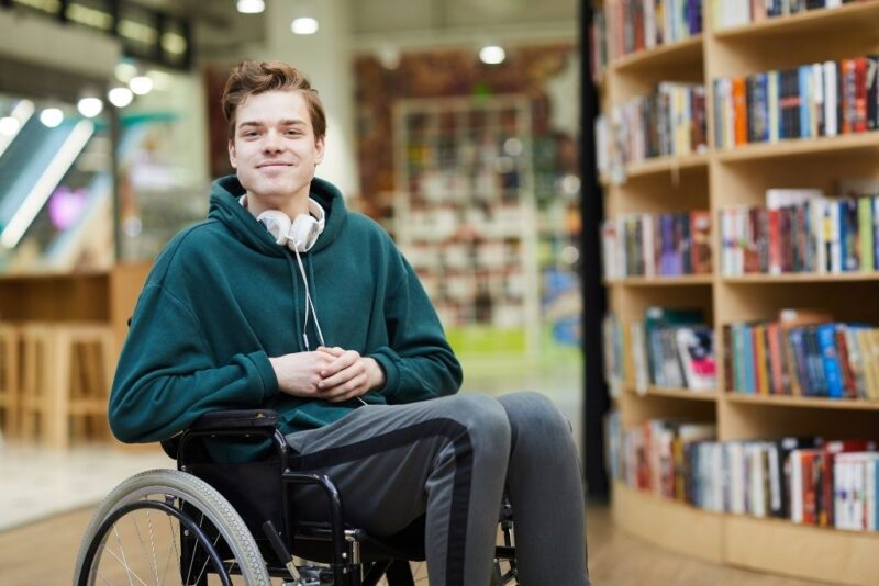 Young male college student in wheelchair at a school library