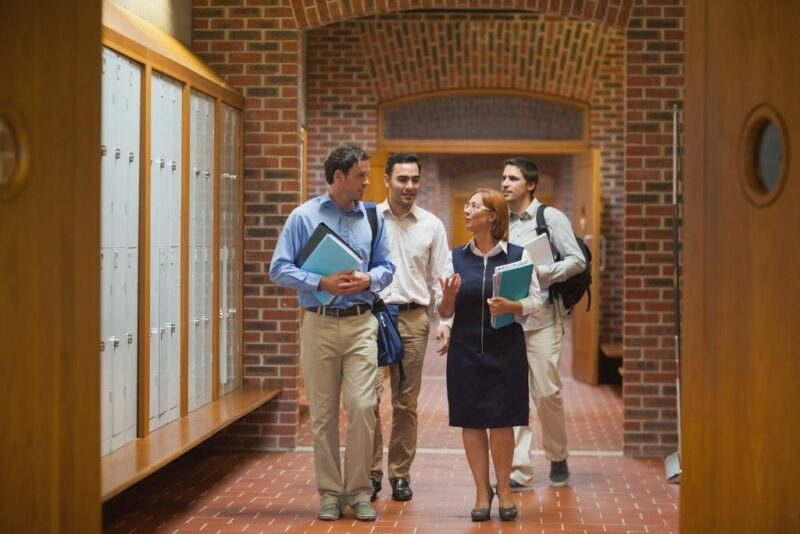 A female communications professor chats with students in a hallway after class