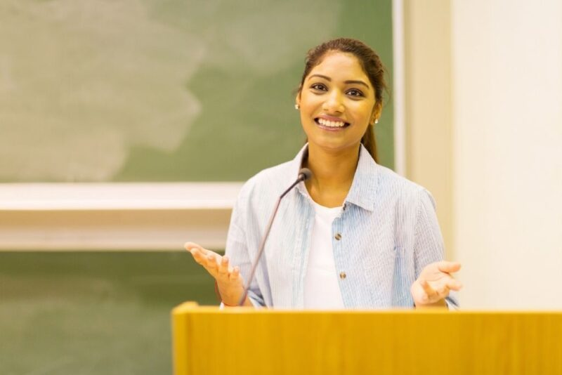 A female communications student speaks at a podium