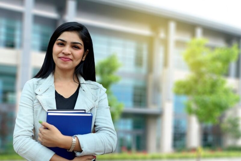 A female undergraduate student stands outside a college building